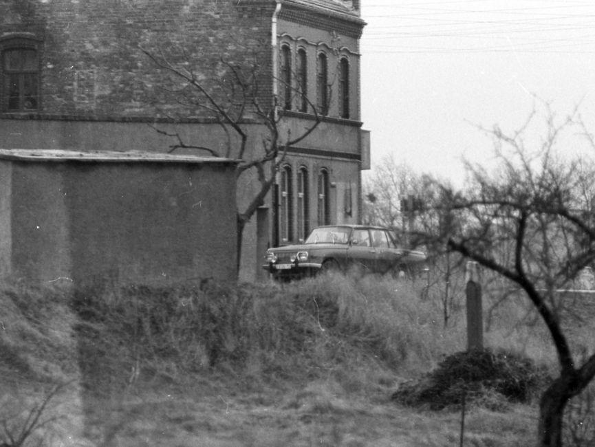 [Auf dem Schwarzweißfoto ist ein dunkler Wartburg zu sehen, der vor einem mehrstöckigen Backsteinhaus vorbeifährt. Der Fotografierende stand hinter einer leichten Anhöhe, auf der linken Bildseite ist ein kleiner Betonflachbau zu sehen.]