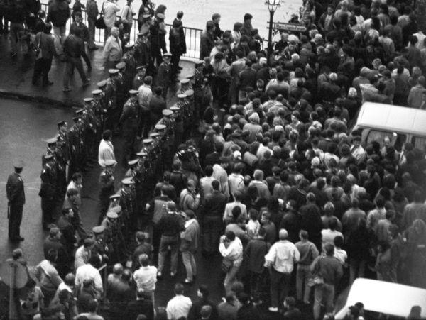 [Das schwarz-weiße Lichtbild zeigt auf der rechten Seite eine Menschenmasse auf der Straße, dazwischen parkende Autos. Aufder linken Seite stehen Polizisten in Doppelreihe zur Abgrenzung. Zwischen ihnen vermutlich Mitarbeiter der Staatssicherheit.]