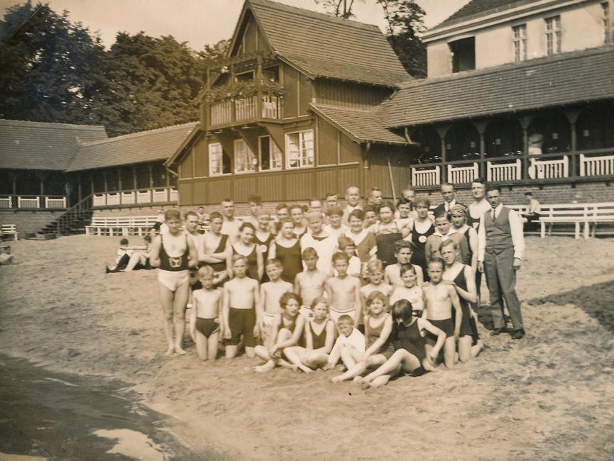 Das Gruppenfoto ist ein schwarz-weißes Lichtbild und zeigt die Personen gemischten Alters, überwiegend in Badebekleidung, am (heutigen) Strandbad Straussee.
