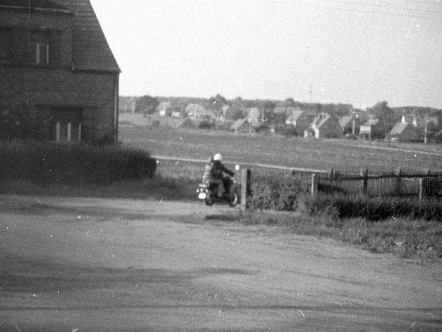 [Das schwarzweiße Lichtbild zeigt die Hausecke eines alleinstehendes mehrstöckiges Backsteinhauses. Davor verläuft eine Sandstraße, zwei Personen auf einem Motorroller fahren von dem Fotografierenden weg. Im Hintergrund sind diverse zusammenstehende Einfamilienhäuser zu sehen.]