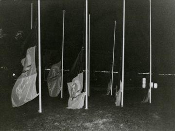 Auf dem schwarz-weißen Lichtbild sind acht Fahnenmasten bei Nacht zu sehen. An allen wurde die Fahne der DDR so weit herunter gelassen, dass sie überwiegend auf dem Boden schleifen. Das Positiv ist Teil einer Fotodokumentation.