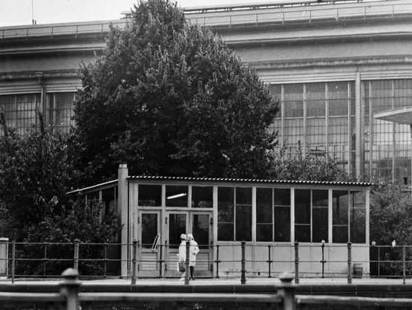 Foto vom Bahnhof Friedrichstraße in Berlin-Mitte. Das Bahnhofsgebäude erscheint nur in einem kleinen Ausschnitt im Bildhintergrund. Davor stehen Bäume und Sträucher. Davor ist ein kleines Häuschen abgebildet. Dabei handelt es sich um eine Grenzschleuse, über welche Mitarbeiter der Staatssicherheit das normale Ausreiseverfahren umgehen konnten. Vor dem Haus befinden sich zwei Menschen.