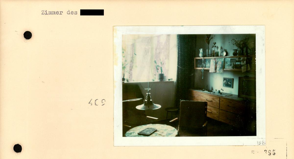 [Es handelt sich um den Ausschnitt einer Fotodokumentation.]  Zimmer des [anonymisiert]  [Stempel: 409] [Das farbige Lichtbild zeigt die Zimmerecke einer konspirativ durchsuchten Wohnung. Im Vordergrund vor einem Fenster ist ein kleiner runder Tisch mit zwei Stühlen sowie einer tief hängenden Deckenlampe zu sehen. Im Hintergrund und direkt in der Ecke ist ein Sideboard aus Holz platziert.]