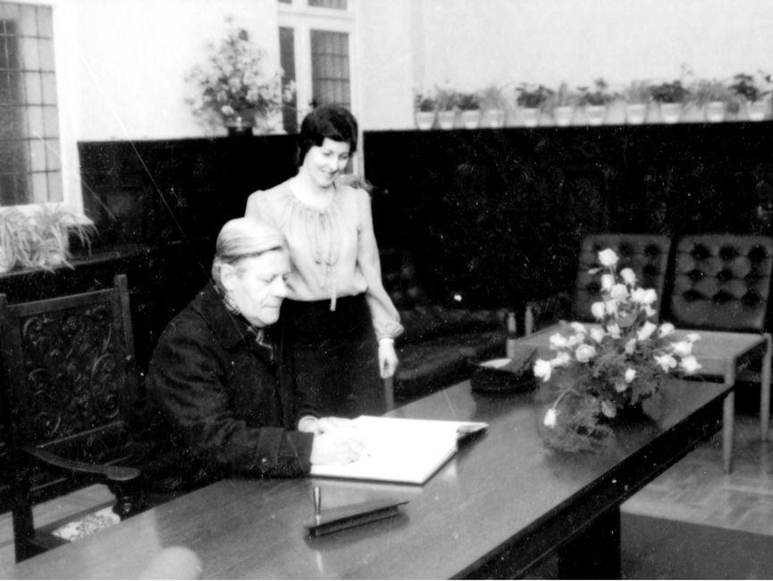 Diese Schwarweißaufnahme zeigt Helmut Schmidt bei seinem Staatsbesuch in der DDR 1981, wie er an einem Schreibtisch sitzend, sich in ein Buch einträgt. Neben ihm steht eine Frau.
