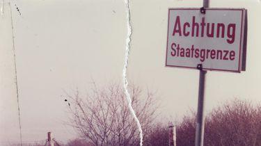 Das zerrissene und wiederhergestellte Bild zeigt den Blick in eine schneebedeckte Winterlandschaft. Dort steht ein Schild: 'Achtung Staatsgrenze'