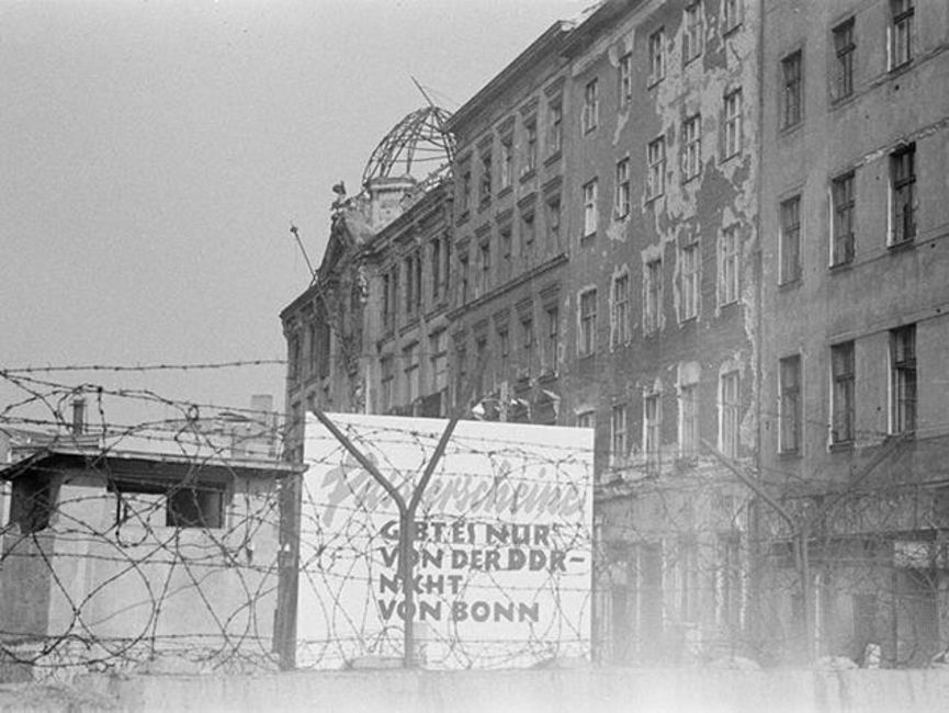 [Durch den Stacheldrahtzaun oberhalb der Mauer sind weitere kriegsgeschädigte Häuser auf der Seite von Berlin (Ost) zu sehen. Es handelt sich um ein schwarz-weißes Lichtbild. Direkt hinter der Mauer ist ein Schild mit folgendem Text aufgestellt.] Passierscheine gibt es nur von der DDR -  nicht von Bonn