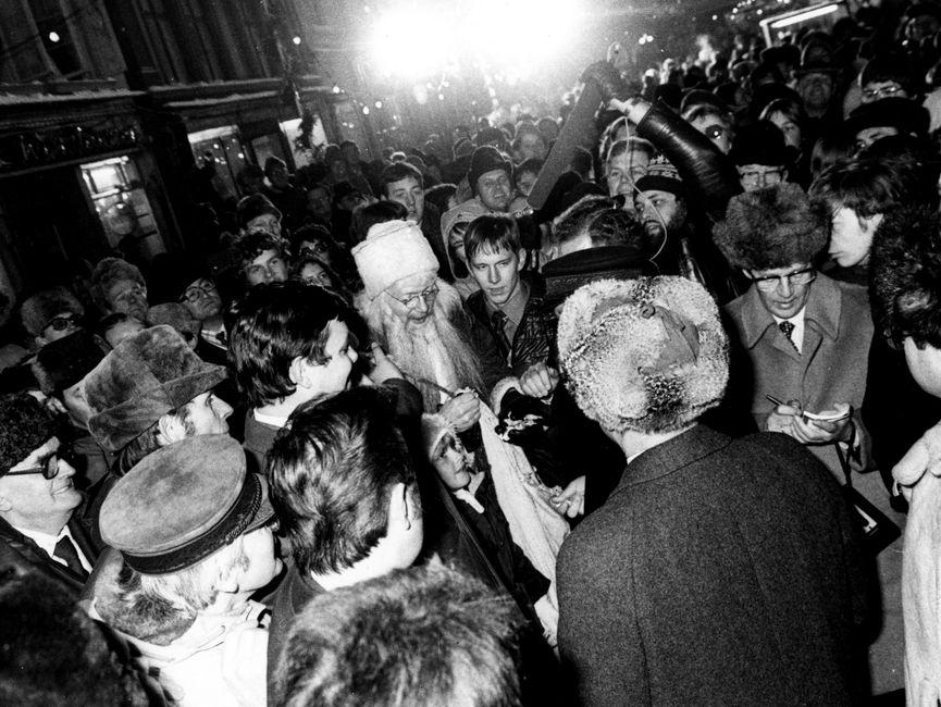 Der Ausschnitt der Schwarzweißaufnahme zeigt Helmut Schmidt und Erich Honecker (von hinten fotografiert) auf dem Güstrower Weihnachtsmarkt. Es hat sich eine große Menschenmenge um die beiden Staatsmänner versammelt. Die Menschenansammlung zieht sich weit bis in die Straße hinein. Vor Erich Honecker und Helmut Schmidt ist auch ein Mann - verkleidet als Weihnachtsmann - zu erkennen. Ein Mann hinter Helmut Schmidt scheint auf einem kleinen Block in der Hand Notizen zu schreiben. Ein anderer Mann hält von hinten ein Mikrofon in Richtung Helmut Schmidt und Erich Honecker hin. Ein Mann unten links im Bild trägt die für Helmut Schmidt typische Schirmmütze.