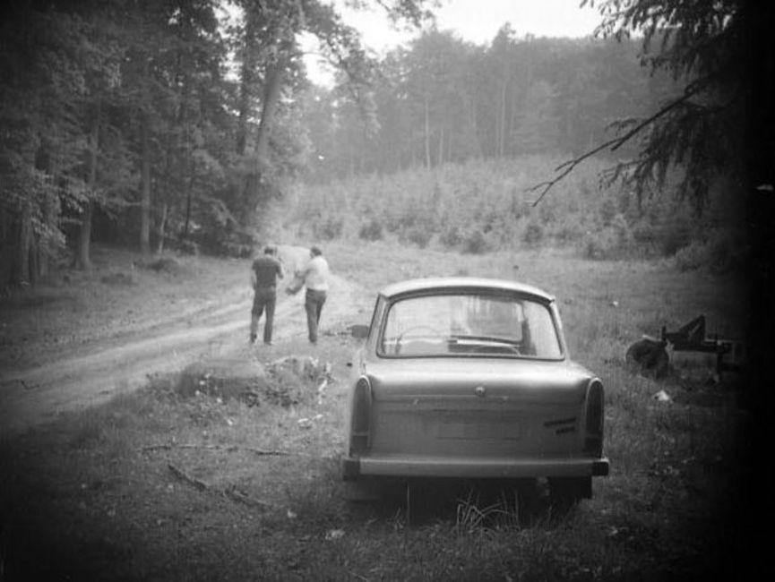 Das schwarz-weiße Lichtbild zeigt einen Waldrand. Auf einem losen Pfad sind zwei Männer von hinten zu erkennen. Im Bildfokus steht das Heck eines Trabant. Die Ecken sind abgedunkelt, vermutlich wurde das Foto verdeckt aufgenommen.