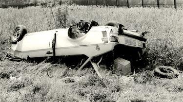 Das stark beschädigte Unfallfahrzeug liegt abseits der Straße auf dem Dach. Daneben sind Reifen und der Inhalt des geöffneten Kofferraums auf der Wiese verstreut.