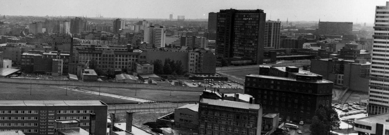 Foto vom Grenzverlauf in Berlin. Im Hintergrund ragt das Axel-Springer-Hochhaus empor.