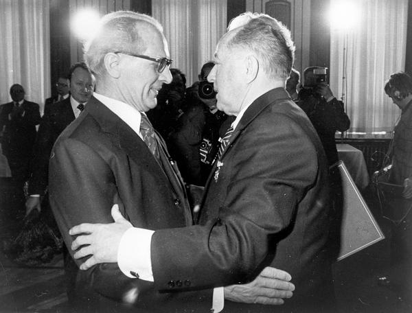 Das Schwarz-Weiß-Bild zeigt Erich Honecker und Erich Mielke, die sich gerade begrüßen und dabei die Hände schütteln.
