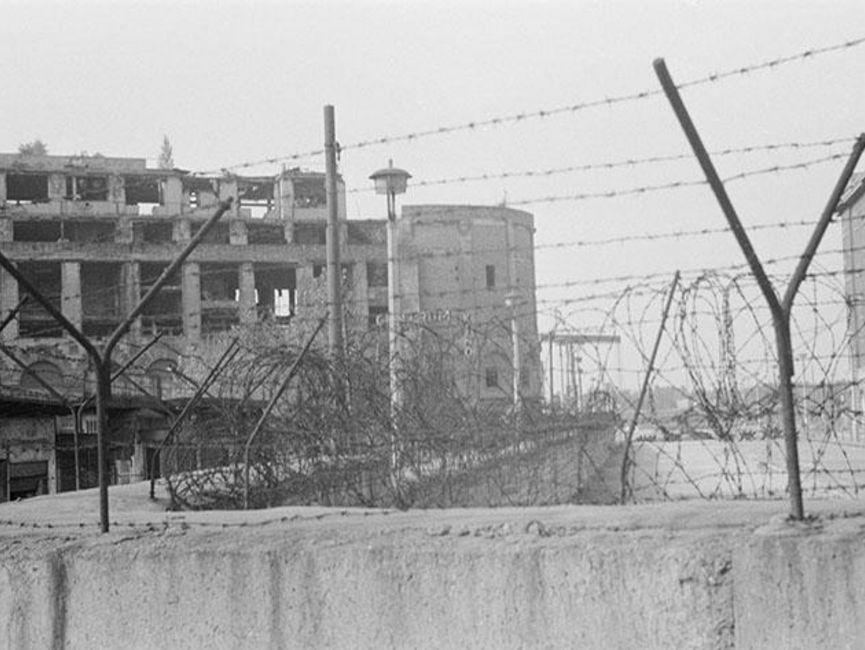 Der Fokus des schwarz-weißen Lichtbilds liegt auf dem Stacheldraht auf einem Mauerabschnitt. Im Hintergrund sind drei Gebäudeschuppen und ein großes, vom Krieg geschädigtes Haus zu sehen.
