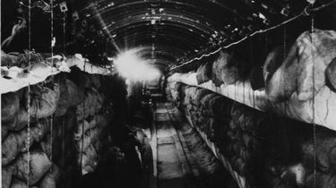 Im Hochkantformat wurde in den langen Tunnel mit der gewölbten Decke hinein fotografiert. Auf beiden Seiten sind Regale voller Leinensäcke.
