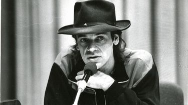 Das Bild zeigt Udo Lindenberg bei der internationalen Pressekonferenz am 25.10.1983 vor seinem Auftritt im Palast der Republik. Das Foto zeigt ein Portrait Lindenbergs, der Sportjacke und einen Hut mit einem kleinen silbernen Stern darauf trägt. Der Künstler spricht gerade in das vor ihm befindliche Mikrofon.