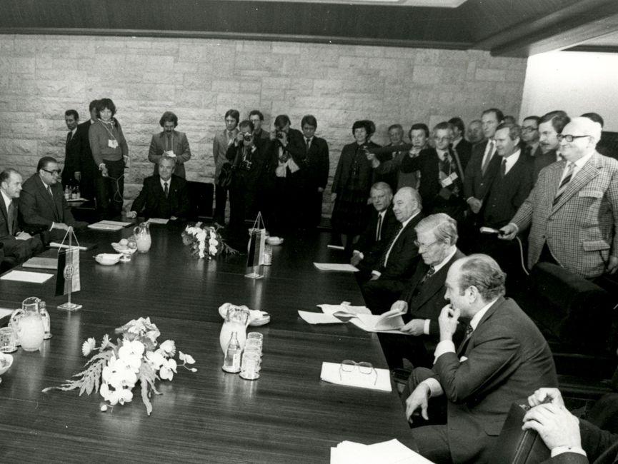 Die Schwarzweißaufnahme zeigt Helmut Schmidt bei der Arbeitsbesprechung der Regierungsdelegationen von BRD und DDR. Hierzu haben sich um einen Besprechungstisch Männer und eine Frau, teils um den Tisch stehend und einige am Tisch sitzend, versammelt. Am rechten Bildrand ist eine zweite Stuhlreihe zu erkennen, die von einigen Männern genutzt wird. Helmut Schmidt blättert gerade in seinen Unterlagen und schaut darauf. Ein Mann hat seine Brille auf sein Schriftstück abgelegt.