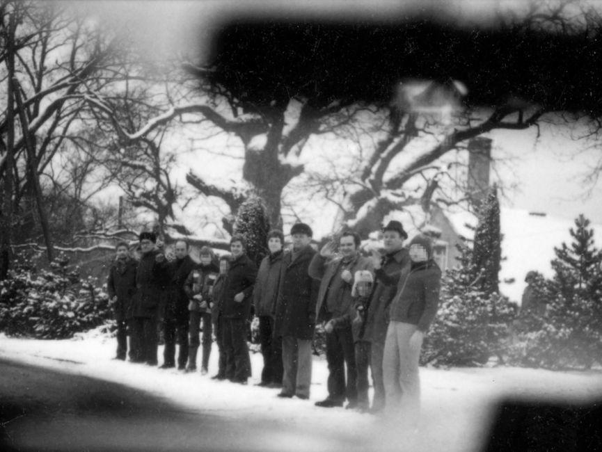 Die Schwarzweißaufnahme zeigt zwölf Zuschauer am Straßenrand in Güstrow während Helmut Schmidts Staatsbesuch in der DDR. Die Zuschauer bestehen aus Erwachsenen und Kindern. Einige der Zuschauer heben die Hand zur Begrüßung. Vermutlich ist die Aufnahme aus einem fahrenden Auto aufgenommen worden.