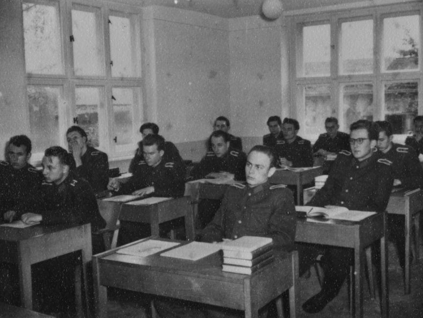 Junge Stasi-Offiziere sitzen in einem Klassenraum an Pulten.