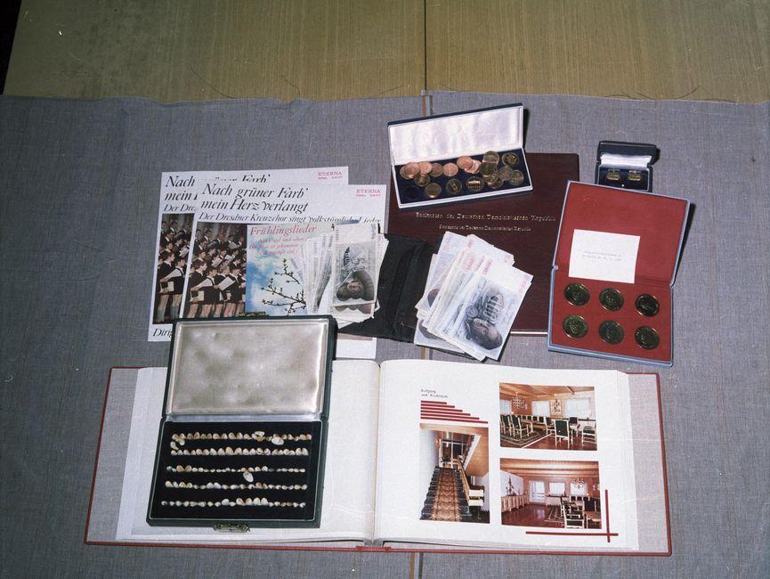 Die Aufnahme zeigt einen Teil eines großen Tisches. Im Hintergrund liegt ein Zettel, dessen Text nicht entziffert werden kann. Im Zentrum des Bildes befinden sich einige für die Aufnahme drapierte Gegenstände: eine Schachtel mit Orden, zwei Schachteln mit Münzen, mehrere 100-DM-Banknoten und eine Schachtel mit Muscheln.