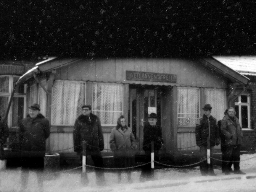 Die Schwarzweißaufnahme zeigt Zuschauer an der Protokollstrecke bei Helmut Schmidts Staatsbesuch in der DDR 1981. Hinter ihnen befindet sich ein einstöckiges Haus. Über dem Eingang des Hauses ist ein Schild auf dem 'Veteranen Treff' geschrieben steht, angebracht.