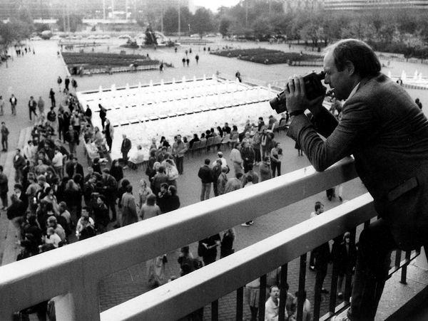 [Im Hintergrund ist eine Menschentraube auf dem Platz am Neptunbrunnen zu erkennen. Von dem Podest des Eingangspavillons des Fernsehturms filmt ein Mann im karrierten Sakko mit einem Camcorder in die Menge herunter. Das Lichtbild ist in schwarzweiß.]
