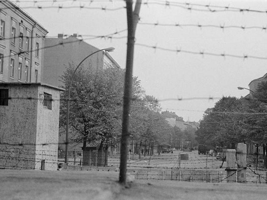 Auf dem schwarz-weißen Lichtbild wurde eine Straße hinter dem Stacheldraht auf der Berliner Mauer fotografiert. Die Straße zwischen den Häuserzeilen wird von Bäumen eingefasst, von den Grenzsicherungsanlagen ist kaum etwas zu erkennen.
