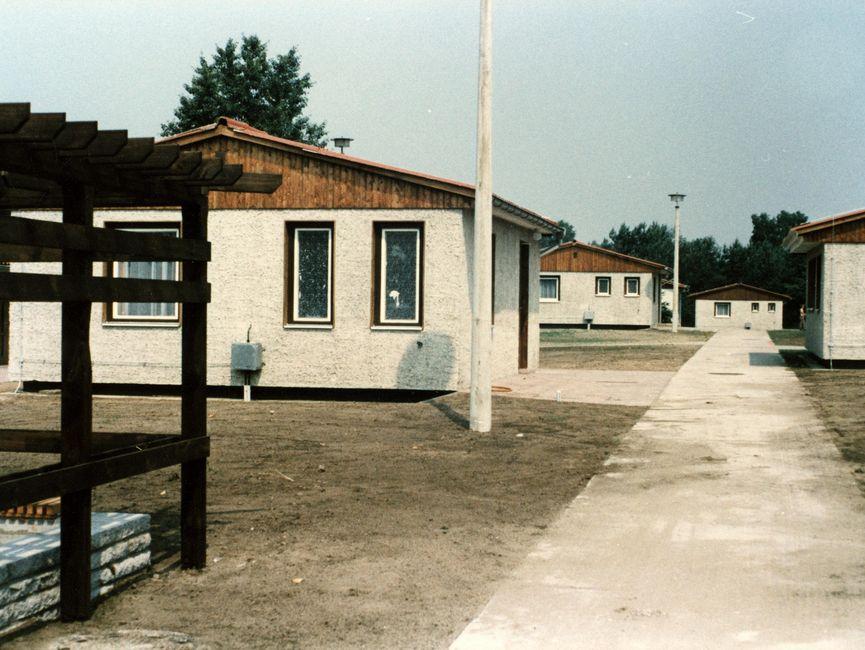 Das Bild zeigt einen Weg, links und rechts davon zweigen weitere Wege ab, die jeweils zu einem Bungalow führen. Links im Vordergrund ist der Teil eines offenen Holzgebäudes zu sehen.