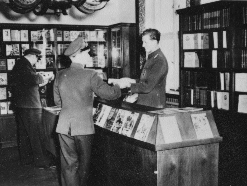 Drei JHS-Angehörige vor mehreren Bücherregalen in der Bibliothek