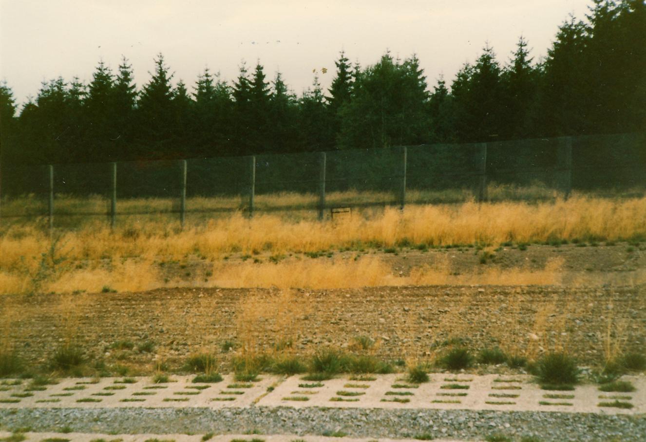 Vom Fahrweg der Grenzsicherungsanlagen aus aufgenommenes Foto eines kleinen Gitters unten im Grenzzaun. Dieses unscheinbare wird durch die hohen Gräser fast verdeckt und erst auf den zweiten Blick wahrgenommen.