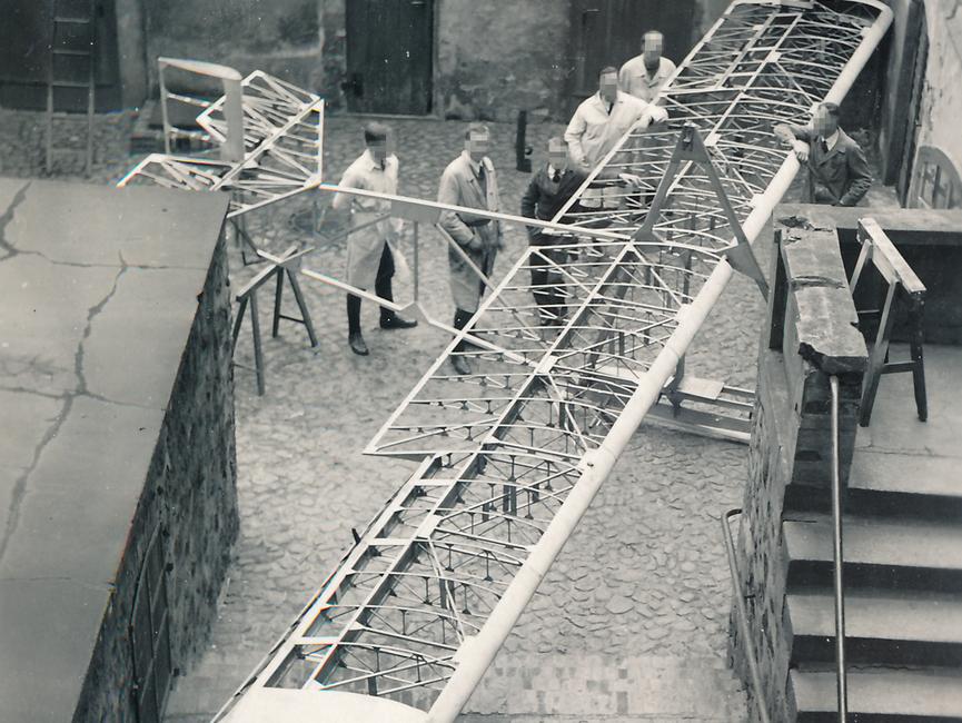 Auf dem schwarz-weißen Lichtbild sieht man das Grundgerüst für einen Gleitflieger. Um ihn herum stehen sechs Männer, alle im Arbeitsmantel. Die Szene wurde in einem gepflasterten Hinterhof in der Draufsicht aufgenommen.