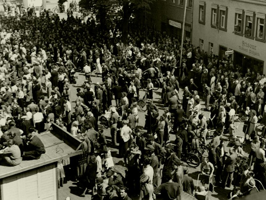 Der selbe Ort in Sömmerda am 17. Juni 1953, diesmal aus einer erhöhten Perspektive. Vorne links ist eine der beiden Bretterbuden zu sehen, auf der noch immer einige junge Männer sitzen. Die Menschenmenge auf dem Platz selbst ist in langsamer Bewegung und nicht mehr so dicht gedrängt.
