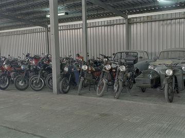 Ein mittels Wellblech überdachter Platz aus Betonplatten wird als Parkplatz genutzt. Vor einer Wand aus Wellblech stehen zahlreiche Motorräder in zwei Reihen in senkrechter Aufstellung. In der hinteren Reihe stehen auch drei Trabis. auf der rechten Seite stehen in der vorderen Reihe auch ein Anhänger, beladen mit Papiertüten, sowie links davon ein Motorrad mit Beiwagen. Das farbige Lichtbild wurde mit einem Weitwinkelobjektiv aufgenommen.