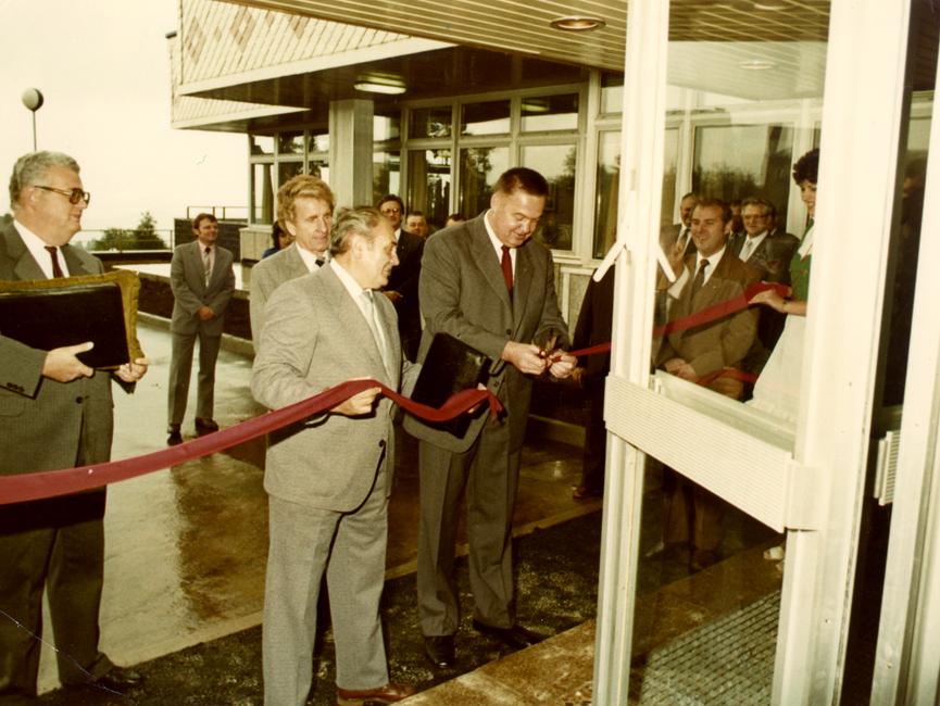 Das farbige Lichtbild wurde durch eine nach außen geöffnete Tür aufgenommen. Von einigen Anwesenden werden Günther Müller und Gerhard Lange dabei beobachtet, wie sie zur Eröffnung ein rotes Band durchschneiden.