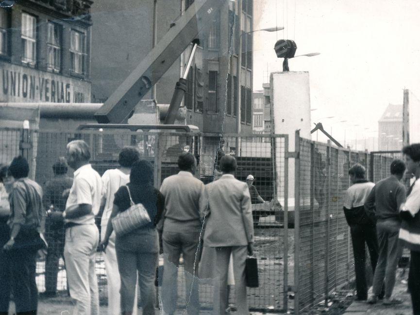 Vor einem Bauzaun am Union-Verlagsgebäude stehen Schaulustige. Dahinter steht ein Kran und versetzt Mauerelemente. Das Foto war mittig zerrissen worden und ist nun manuell rekonstruiert.