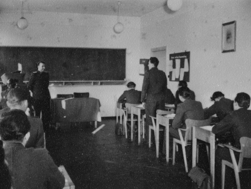 Studenten der JHS an Pulten in einem Seminarraum. Einer der Studenten steht vor seinem Pult.