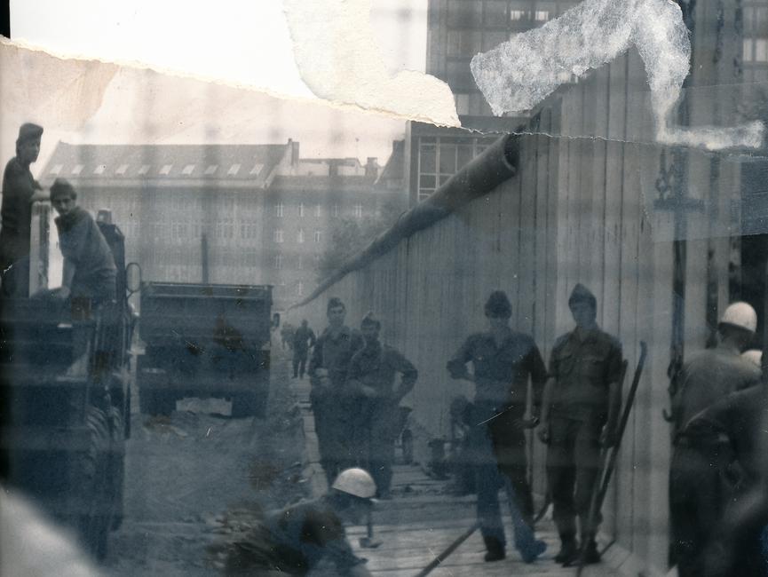 Das schwarz-weiße Lichtbild ist durch die Maschen eines Bauzauns aufgenommen worden und zeigt den Kontrollstreifen der Grenzanlagen. Das Foto dokumentiert Bauarbeiten an der Berliner Mauer. Es stehen mehrere uniformierte Männer um zwei Bauarbeiter herum, während ein Mauerstück mittels Kran abgesenkt wird. Im Hintergrund ist das Hochhcaus des Axel Springer Konzerns zu sehen. Das Foto war mittig zerrissen worden und ist nun manuell rekonstruiert.