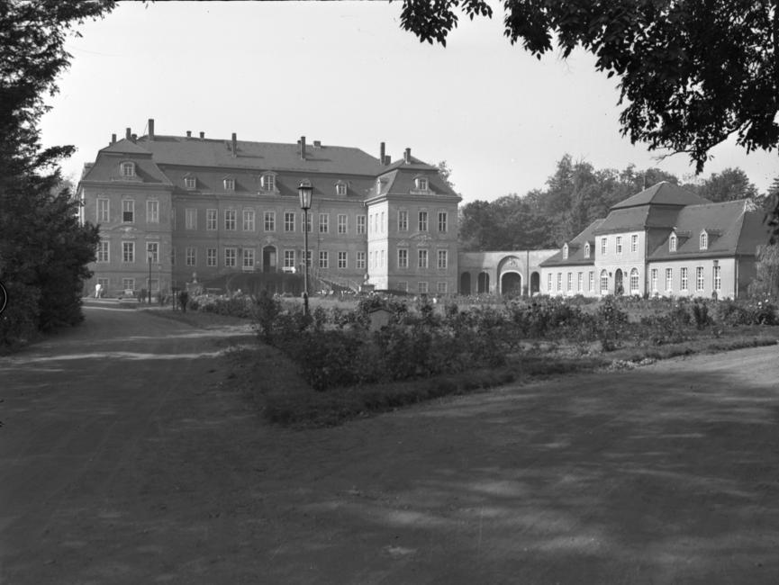Auf dem schwarz-weißemn Lichtbild ist eine Außenaufnahme des Schloss Nischwitz, Gemeinde Thalwitz, zu sehen. AUf der rechten Seite gliedert sich ein etwas kleineres Gebäude an. Im Vordergrund ist ein mit Blumen gesäumter Rasen, umgeben von Parkwegen, zu sehen.