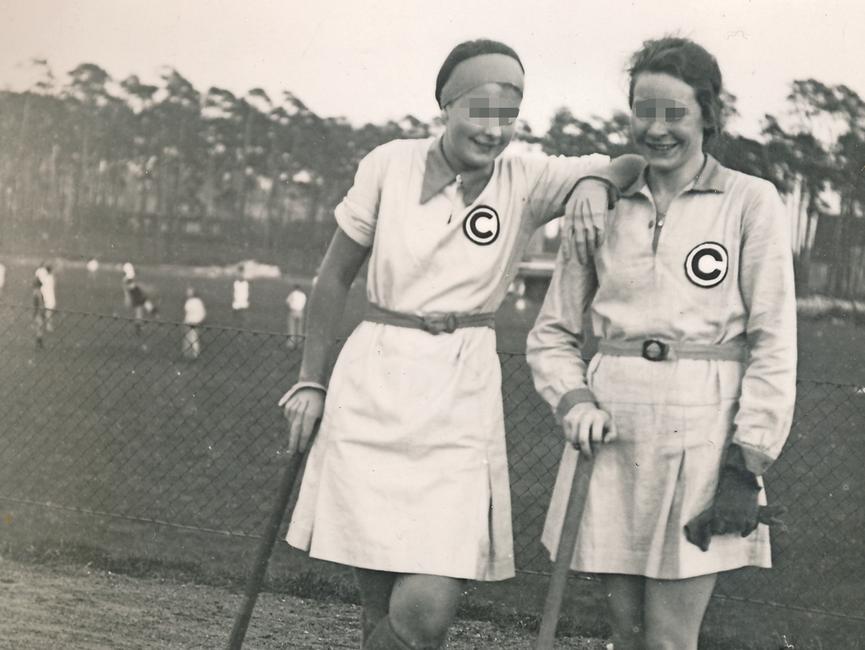 Im Bildmittelpunkt des schwarz-weißen Lichtbildes posieren zwei junge Frauen mit Hockeyschlägern. Auf ihrem kurzen Sportdress prangt auf der rechten Seite auf Brusthöhe ein schwarzes, eingekreistes C. Im Hintergrund ist ein Spielfeld vor Kiefern zu sehen.