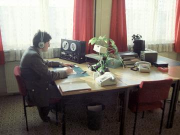 [Das farbige Lichtbild zeigt drei Tische, die zu einem großen Arbeitsbereich zusammen geschoben wurden. Daran sitzt ein Mann in Uniform, der im Profil zu sehen ist. Er trägt Kopfhörer, rechts von ihm steht ein Tonbandgerät und vor ihm liegen Papierbögen für Notizen. Sein Schreibtischteil wirkt besonders aufgeräumt, trotz der Tasse neben dem Tischtelefon. Ihm gegenüber ist ein gleichwertiger Arbeitsplatz eingerichtet, dazwischen steht eine Ablage und ein weiteres Tischtelefon.]