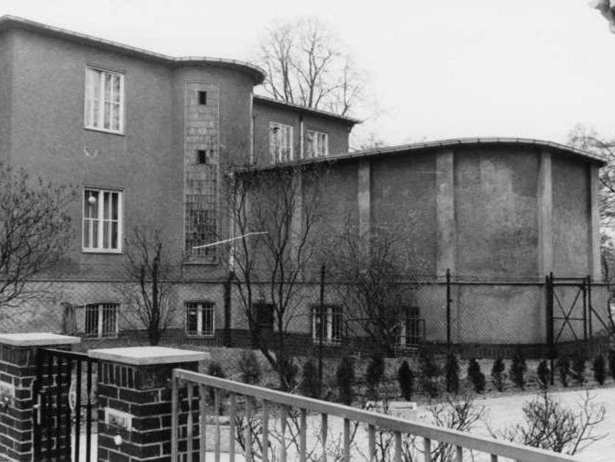 Ein auf Höhe des Nachbargrundstücks aufgenommenes schwarz-weißes Lichtbild zeigt den fensterlosen Teil des Anbaus. Die beiden Grundstücke sind deutlich durch einen Maschenzaun abgegrenzt.