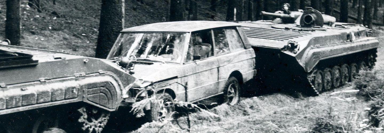 Das Bild zeigt einen von zwei Panzerwagen eingekeilten Jeep auf einem Waldweg.