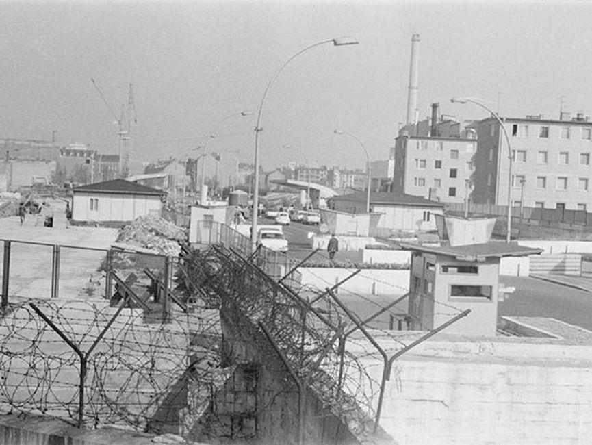Das schwarz-weiße Lichtbild wurde oberhalb des Stacheldrahtes der Mauer aufgenommen. Zu sehen ist die Grenzübergangsstelle Heinrich-Heine-Straße mit Blick gen Berlin (Ost). Auf der linken Seite liegt ein braches Grundstück, auf dem Schuttberge zu aufgehäuft sind.