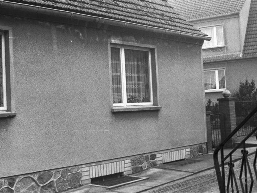 Das schwarz-weiße Lichtbild zeigt eine Hausecke eines Einfamilienhauses, der Haussockel ist mir Natursteinen gefliest. Zu sehen ist eines der Fenster sowie der anschließende Zaun des Nachbargrundstückes. In der rechten Bildecke sieht man das Schmiede-eiserne Geländer einer Treppe.
