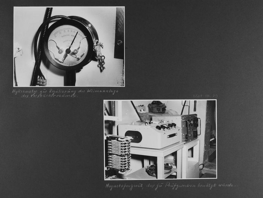 [Bild 1: Zu sehen ist die Nahaufnahme einer großen Messuhr eines Hygrographen. An der rechten Seite ist ein Schloss samt Schlüsseln zu sehen. Mit einem Gummischlauch ummantelte Leitungen enden an der Oberseite in dem gerät, die Leitungen sind in einer Klemme verschraubt.] [handschriftliche Ergänzung: Hykrometer zur Regulierung der Klimaanlage des Verstärkerraumes.]  [Bild 2: Zu sehen sind zwei Tischelemente, die an einen Verteilerabschnitt grenzen. Auf dem ersten Tisch steht ein leeres Tonbandgerät, auf dem Tisch dahinter steht ein weiteres elektrisches Gerät.] [handschriftliche Ergänzung: Magnetofongerät, das zu Prüfzwecken benutzt wurde...]