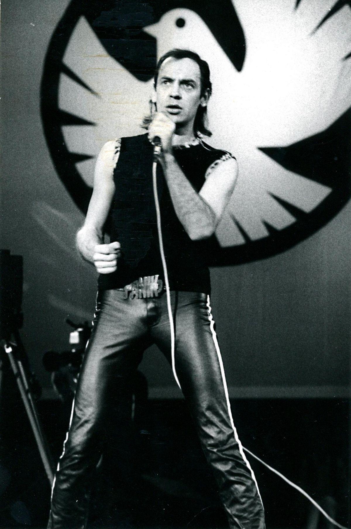 Das Bild zeigt Udo Lindenberg während seines Konzertes im Palast der Republik am 25. Oktober 1983. Der Sänger steht auf der Bühne, hält ein Mikrofon in der Hand und singt. Er trägt ein ärmelloses schwarzes Shirt und eine schwarze Lederhose. Diese wird gehalten von einem Gürtel mit einer Gürtelschnalle, die aus dem Schriftzug 'Panik' besteht. Hinter Lindenberg ist eine große, an die Wand angebrachte Friedenstaube zu erkennen.