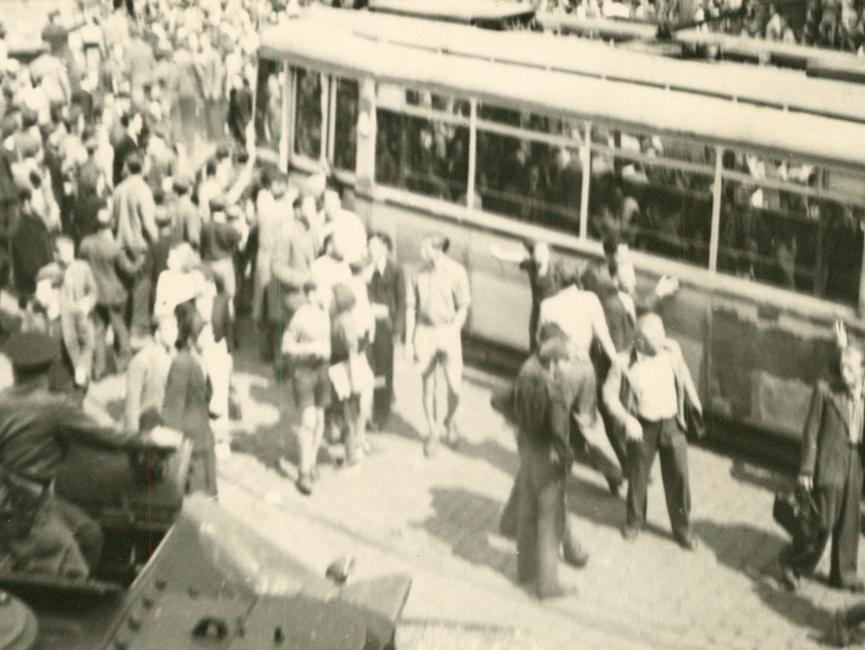 Demonstranten bewegen Straßenbahnwagen, um damit die sowjetischen Panzer zu blockieren.