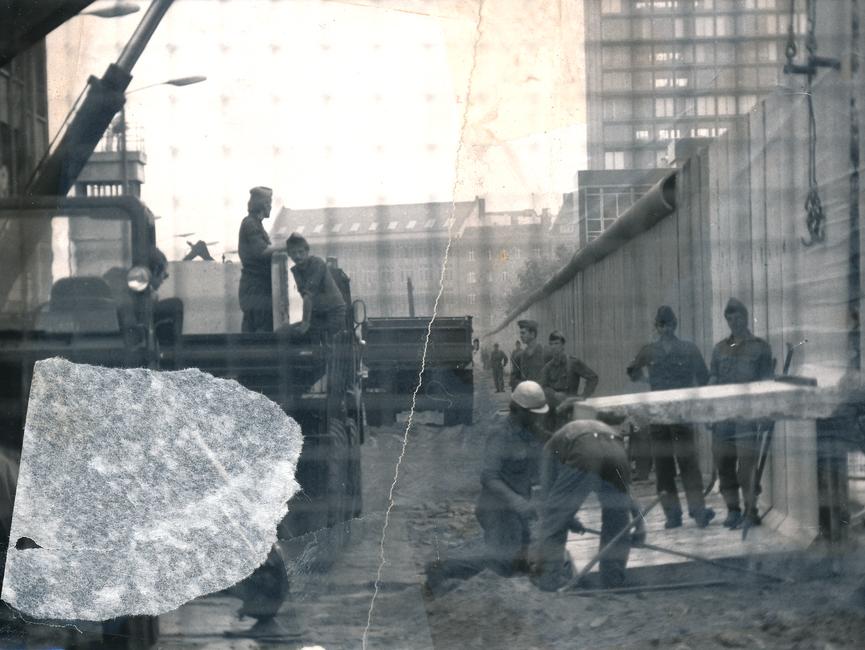 Das schwarz-weiße Lichtbild ist durch die Maschen eines Bauzauns aufgenommen worden. Mit Blick in den Ostteil der Stadt wurden die Bauarbeiten an der Berliner Mauer dokumentiert. Es stehen mehrere uniformierte Männer um zwei Bauarbeiter herum, während ein Mauerstück mittels Kran abgesenkt wird. Das Foto war mittig zerrissen worden und ist nun manuell rekonstruiert. Die Fotoschschicht hat sich auf der linken Seite anteilig gelöst.