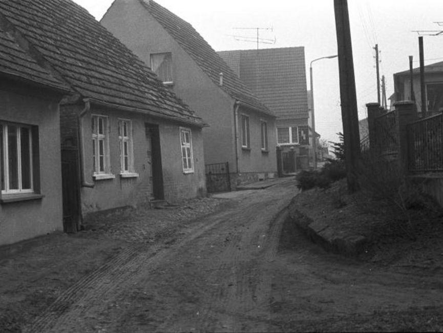 Auf dem schwarz-weißen Lichtbild ist eine unbefestigte Gasse zu sehen, die zwischen zwei Häuserreihen verläuft. Bei den Häusern handelt es sich um Einfamilienhäusern mit Spitzdächern und haben keine Vorgärten.