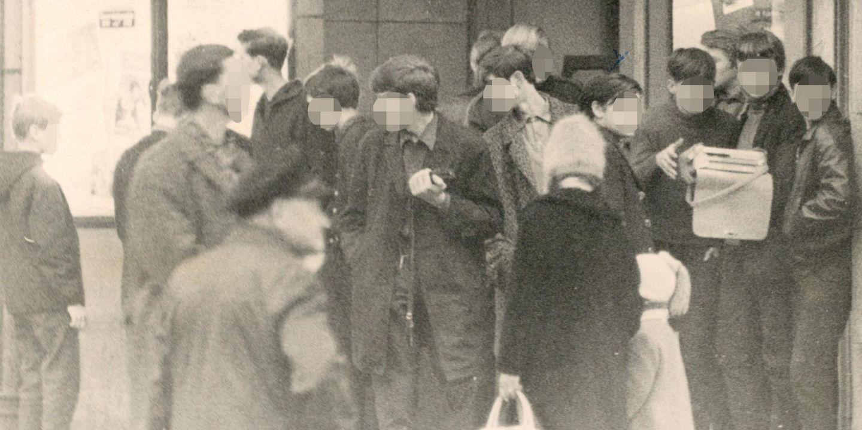 schwarzweiß Aufnahme; eine Gruppe von circa 13 Jugendlichen steht auf der Straße bzw. im Eingangsbereich eines Kinos am S-Bahnhof Schönhauser Allee in Berlin; ein Jugendlicher hält ein Kofferradio in der Hand.