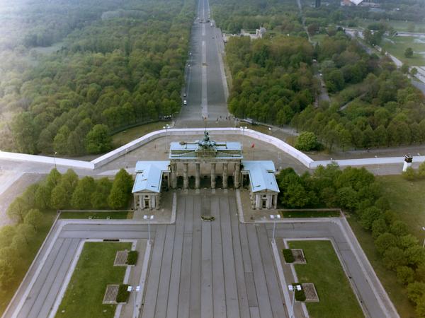 Luftaufnahme des Brandenburger Tors und des Pariser Platzes. Links und rechts davon wehen rote Fahnen. Rechts des Brandenburger Tors ist ein Wachturm zu sehen. Hinter dem Brandenburger Tor verläuft der Grenzstreifen und die Mauer. Dahinter erstreckt sich der Tiergarten und die Straße des 17. Juni. Die Siegessäule ist im oberen Bildabschnitt zu erkennen. Am rechten Bildrand ist die Kongresshalle, das heutige Haus der Kulturen der Welt, abgebildet. Am Horizont ist Westberlin zu sehen. Dem Blattbewuchs der Bäume nach zu urteilen scheint das Foto im Sommer aufgenommen worden zu sein.