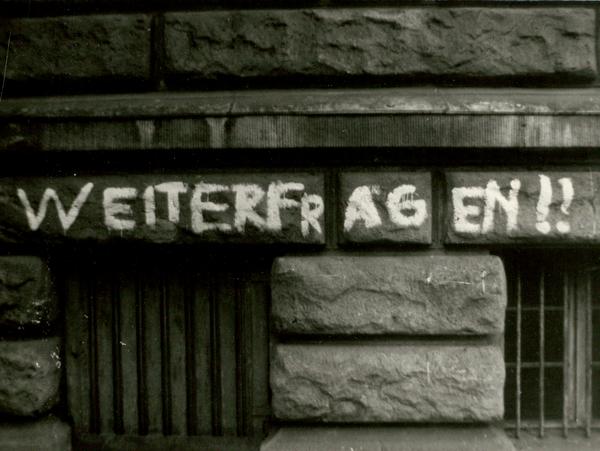 Hauswand der Carl-von-Ossietzky-Schule mit der aufgemalten Losung 'Weiterfragen!!'
